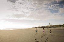 Drei Kinder laufen über Strand — Stockfoto
