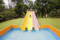 Children playing in pool with water slides — Stock Photo