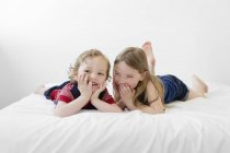 Brother and sister lying on bed — Stock Photo