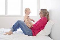 Мать с смеется девочку в коленях — стоковое фото