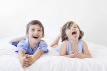 Playful siblings lying side by side — Stock Photo