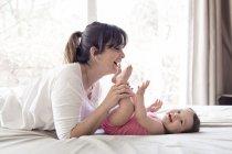 Femme jouant avec la petite fille au lit — Photo de stock