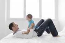 Man lying with baby on stomach — Stock Photo