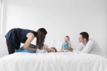 Сім'я разом грають на ліжку — стокове фото