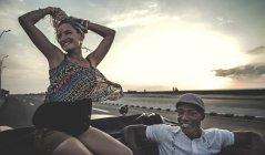 Чоловік і жінка, їзда в класичний Конвертована автомобіль на вершині спинку сидіння — стокове фото