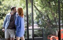 Пара, стоящая на балконе поцелуи — стоковое фото