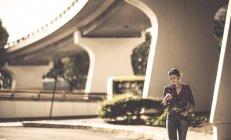 Donna a piedi sotto un ponte stradale — Foto stock