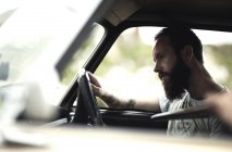 Bearded man sitting in car. — Stock Photo