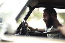 Uomo barbuto seduto in macchina . — Foto stock