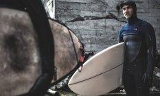 Серфер, стоящий у деревянного здания — стоковое фото