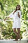 Woman wearing bathrobe standing on balcony. — Stock Photo