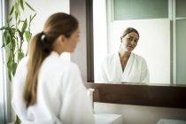 Женщина, стоя перед зеркало в ванной — стоковое фото