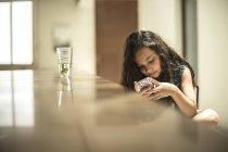 Девушка, сидящая, глядя на мобильный телефон — стоковое фото
