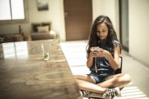 Girl sitting looking at mobile phone — Stock Photo