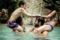 Діти на плечах дорослих у басейні — стокове фото