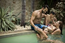 Family hugging in swimming pool. — Stock Photo