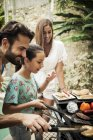 Familien stehen am Grill — Stockfoto
