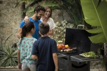 Family standing at barbecue — Stock Photo