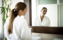 Жінка стоїть перед дзеркало — стокове фото