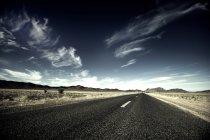 Сельская дорога через пустынный ландшафт — стоковое фото