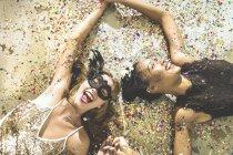 Молоді жінки, лежачи на килимі конфетті — стокове фото