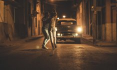 Man and woman dancing together in front of classic car in street at night. — Stock Photo