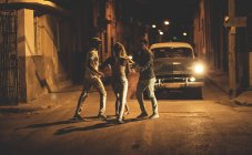 Group of people dancing in front of a classic car in street at night. — Stock Photo