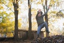 Garçon sautant en gros tas de feuilles. — Photo de stock