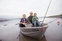 Mature man and boys sitting in fishing boat at Ashokan Reservoir — Stock Photo
