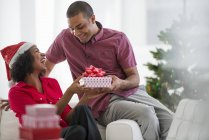 Man giving woman Christmas present while sitting on sofa in room interior — Stock Photo