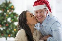 Pareja posando con sombrero de Santa frente a árbol de Navidad - foto de stock
