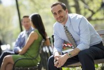 Man in suit looking in camera while sitting on park benches with colleagues — Stock Photo