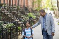 Батько і син, дивлячись один на одного під час прогулянки разом на вулиці в місті — стокове фото