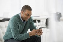 Man checking smartphone on sofa in office — Stock Photo