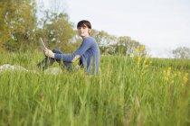 Vista laterale della donna seduta sull'erba con tablet digitale . — Foto stock