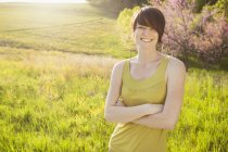 Woman with arms folded standing in grassy field in spring. — Stock Photo