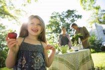 Mädchen mit großen Erdbeerfrüchten und Erwachsenen im Hintergrund — Stockfoto