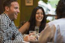 Amigos sentados alrededor de la mesa en la cafetería y tomando bebidas . - foto de stock