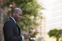 Side view of man in suit checking phone. — Stock Photo