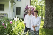 Mature couple in white shirts standing together among flowers in yard. — Stock Photo