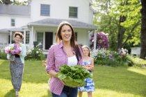 Familie von drei Generationen spaziert auf dem Rasen mit frisch gepflückten Blumen, Obst und Gemüse — Stockfoto
