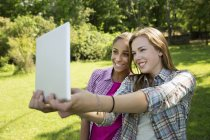 Two young women taking selfie with digital tablet in garden — Stock Photo
