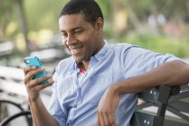 Man sitting on a bench using a smartphone. — Stock Photo