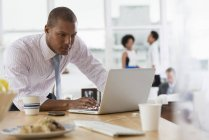 Man using laptop on desk in office with unrecognizable colleagues in background — Stock Photo