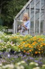 Woman working in plant nursery using a digital tablet. — Stock Photo
