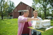 Mature man with adult son looking at house model in green yard — Stock Photo