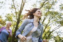 Low angle view of woman running in park with grandmother — Stock Photo