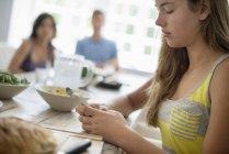 Девушка-подросток проверяет смартфон за обеденным столом с людьми на заднем плане . — стоковое фото