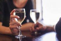 Close-up de copos de vinho em refrigerados branco as mãos do casal sentado no bar. — Fotografia de Stock