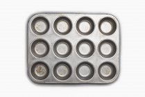 Well used seasoned muffin tin on white background. — Stock Photo